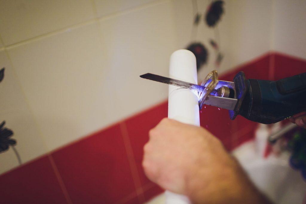 A plumber fixes a water faucet on a water pipe. Pepair plumbing background.