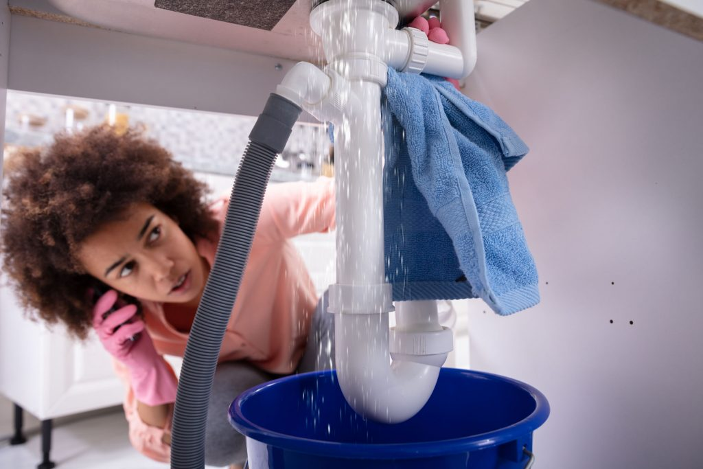 Worried Woman Calling Plumber To Fix Sink Pipe Leakage